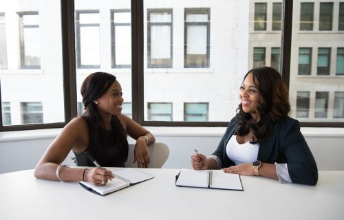 two Black women smiling at work